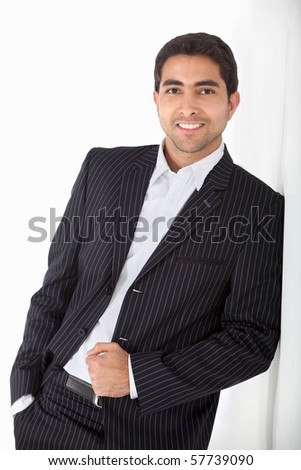 Confident business man leaning against a wall and smiling