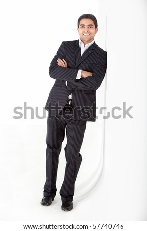 Confident business man leaning against a wall and smiling - stock photo