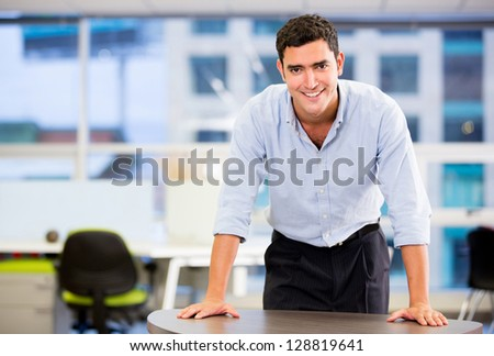 Confident business man smiling at the office - stock photo