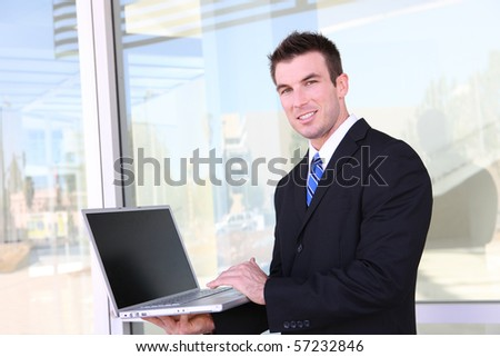 Confident business man working in office on laptop computer - stock photo