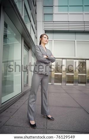 Confident business manager woman standing and looking, full length portrait outside of modern buildings. - stock photo