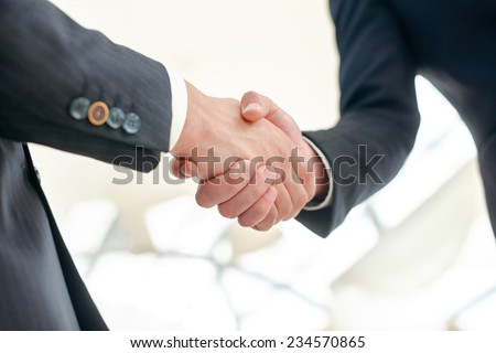 Confident business partners handshaking. Two Confident businessman shake hands with each other in the business office view from below - stock photo