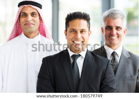 confident business partners looking at camera with indian leader in front - stock photo