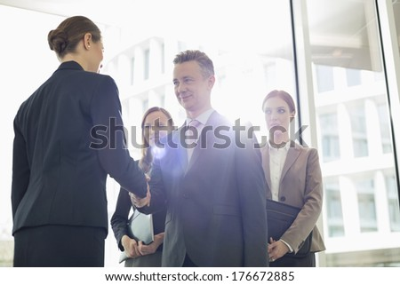 Confident business partners shaking hands in office - stock photo