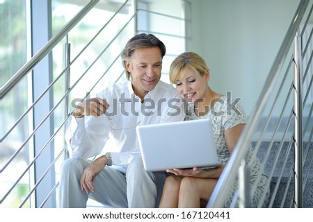Confident business partners sitting on stairs in office building and discussing work, computer, smiling, mature businessman - stock photo