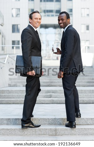 Confident business people. Full length of two cheerful business men looking over shoulder and smiling while standing on staircase - stock photo