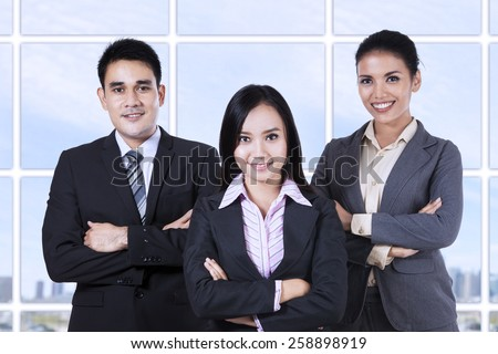 Confident business people looking at camera smiling - stock photo