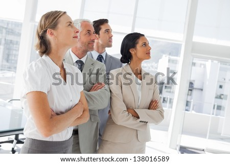 Confident business people looking at the same way in the workplace - stock photo