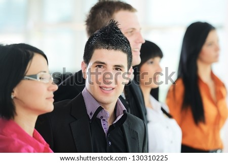 Confident business people posing and looking (only one in row looking at camera) - stock photo