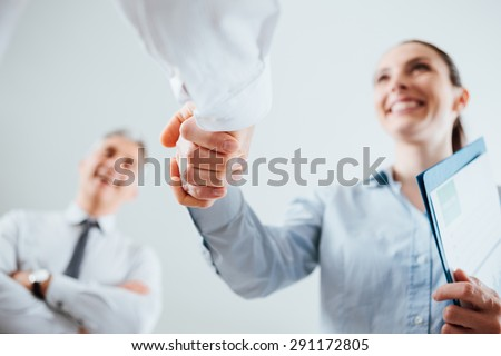 Confident business people shaking hands and woman smiling, recruitment and agreement concept - stock photo