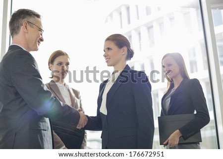 Confident business people shaking hands in office - stock photo
