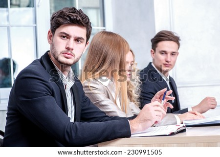 Confident business. Serious businessman sitting at table and looking strictly into the camera while his colleague businessmen talking in the background - stock photo