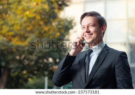 Confident business talk. Cheerful smiling caucasian young man in formal wear talking on the mobile phone and looking away while standing outdoors and against building structure outdoors - stock photo