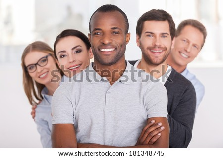 Confident business team. Cheerful young African man keeping arms crossed and smiling while group of people standing behind him in a row and looking at camera - stock photo
