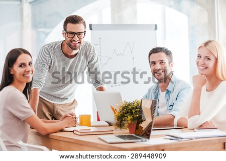 Confident business team. Group of cheerful business people in smart casual wear sitting at the desk together and smiling - stock photo