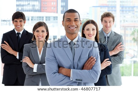 Confident business team standing with folded arms in the office