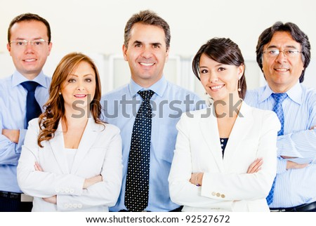 Confident business team with arms crossed at the office - stock photo
