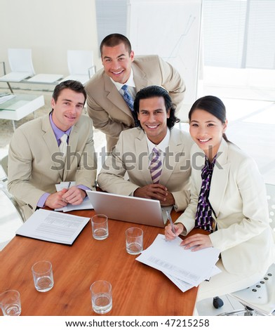 Confident business team working at a computer in a office - stock photo