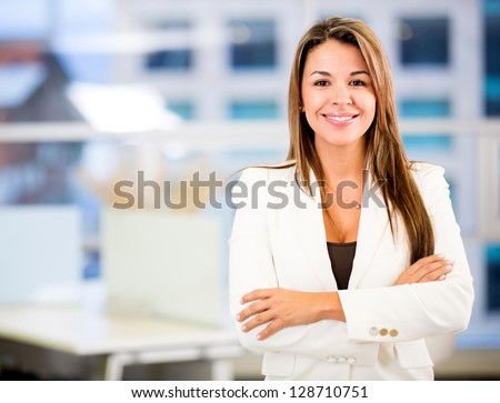 Confident business woman at the office with arms crossed - stock photo