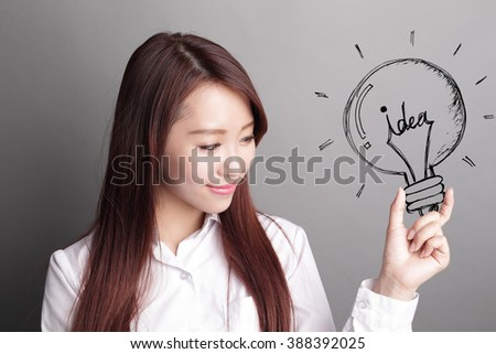 confident business woman hold light bulb isolated over gray background, asian beauty - stock photo