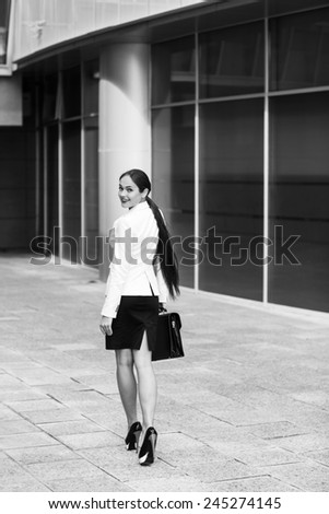 Confident business woman holding briefcase and walking in modern city. - stock photo