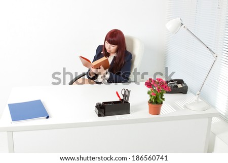 Confident business woman in a modern office reading book - stock photo