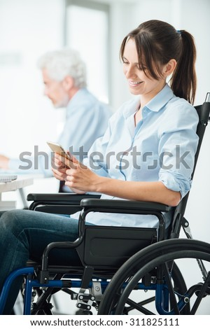 Confident business woman in wheelchair working at office desk and texting with her mobile phone, disability and employment concept
