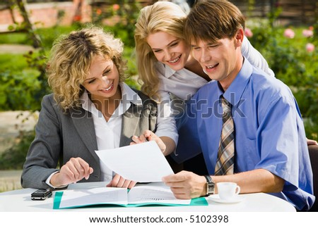 Confident business woman is explaining the correct way of report to her colleagues outside - stock photo