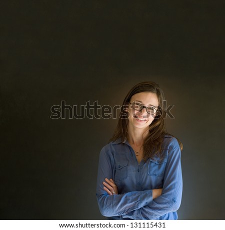 Confident business woman or teacher with glasses and arms crossed against a dark blackboard background - stock photo