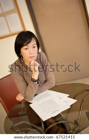Confident business woman reading paper on desk in office.