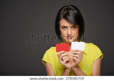 Confident business woman showing blank credit cards in both hands, over gray background - stock photo