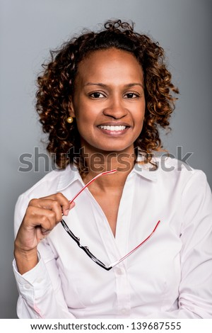 Confident business woman smiling andholding glasses - stock photo