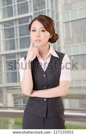 Confident business woman stand in outside of office and look at you.