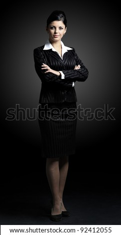 Confident business woman standing full length in black suit - stock photo