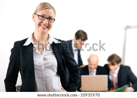 Confident business woman standing in front of her colleagues; selective focus on woman - stock photo