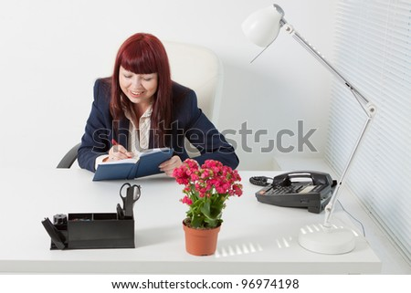 Confident business woman writes in her diary - stock photo