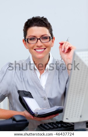 Confident business woman writing on her agenda in the office - stock photo