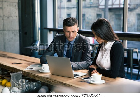 Confident businessman and attractive businesswoman working on laptop together in cafe - stock photo