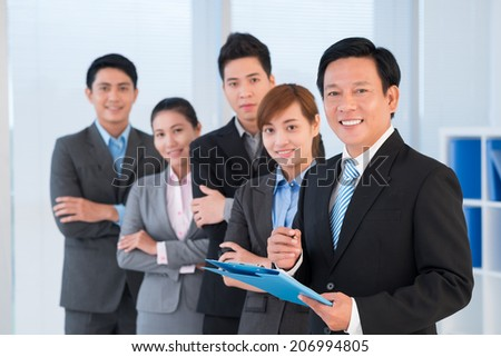 Confident businessman and his team looking at the camera - stock photo