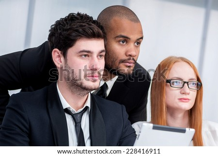 Confident businessman at meeting in office. Three smiling successful businessmen sitting at table in office while discussing their business doings. Young people talking in office