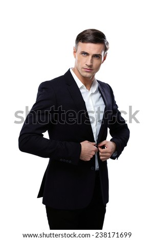 Confident businessman buttoning his jacket isolated on a white background