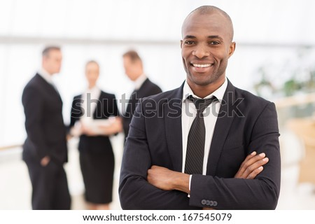 Confident businessman. Cheerful young African man in formalwear keeping arms crossed and smiling while his colleagues standing on background - stock photo