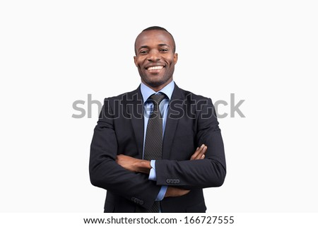 Confident businessman. Cheerful young African man in formalwear keeping arms crossed and smiling at camera while standing against white background - stock photo