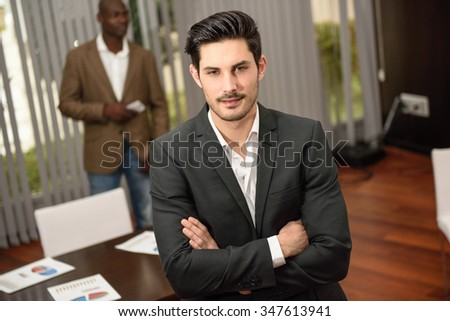Confident businessman. Cheerful young caucasian man in formalwear keeping arms crossed and smiling while his black colleague standing on background using a smart phone - stock photo