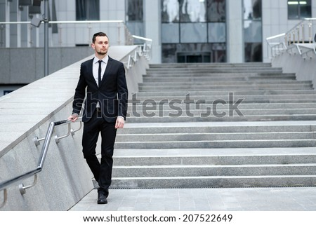 Confident businessman coming down the stairs. Young man in a suit is going to work
