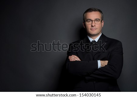 Confident businessman. Confident middle-age man in formalwear keeping his arms crossed and looking at camera while standing isolated on grey - stock photo