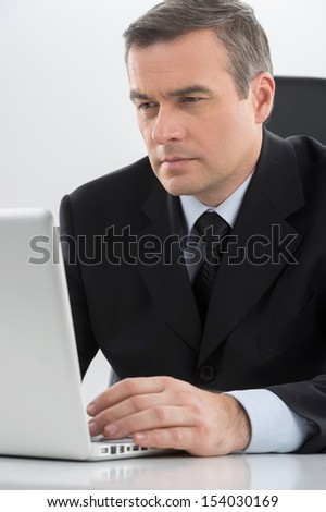 Confident businessman. Confident middle-age man in formalwear working at the computer while sitting at his working place - stock photo