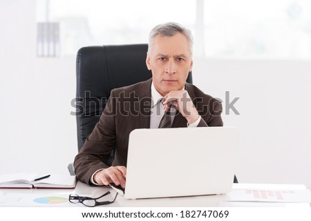 Confident businessman. Confident senior man in formalwear working on laptop and looking at camera while sitting at his working place - stock photo
