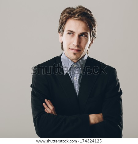 Confident businessman deep in thought standing with his arms folded looking up to the side with an intense speculative expression, on grey - stock photo