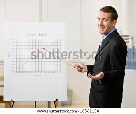 Confident businessman explaining financial analysis chart - stock photo